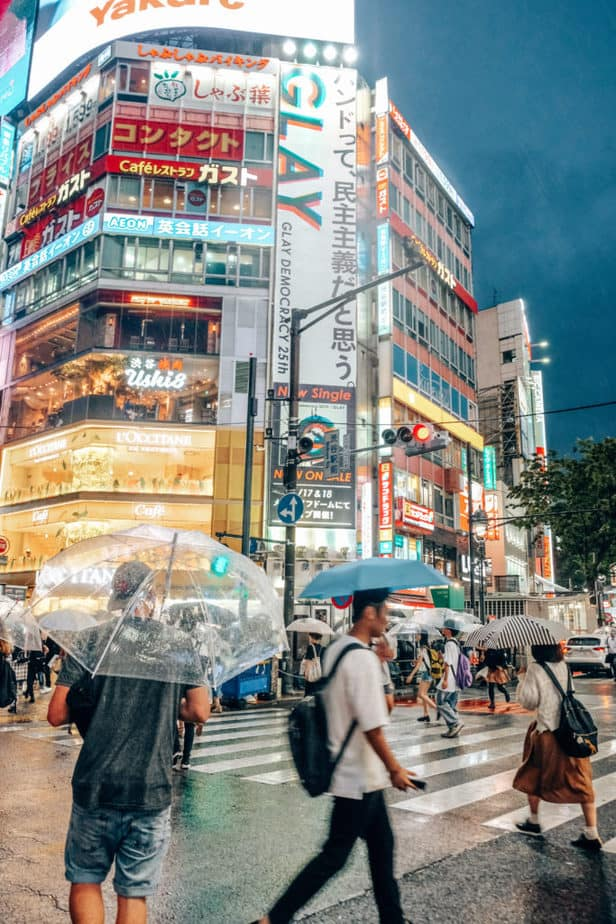 A man with an umbrella walking through Shibuya Crossing at night in Japan
