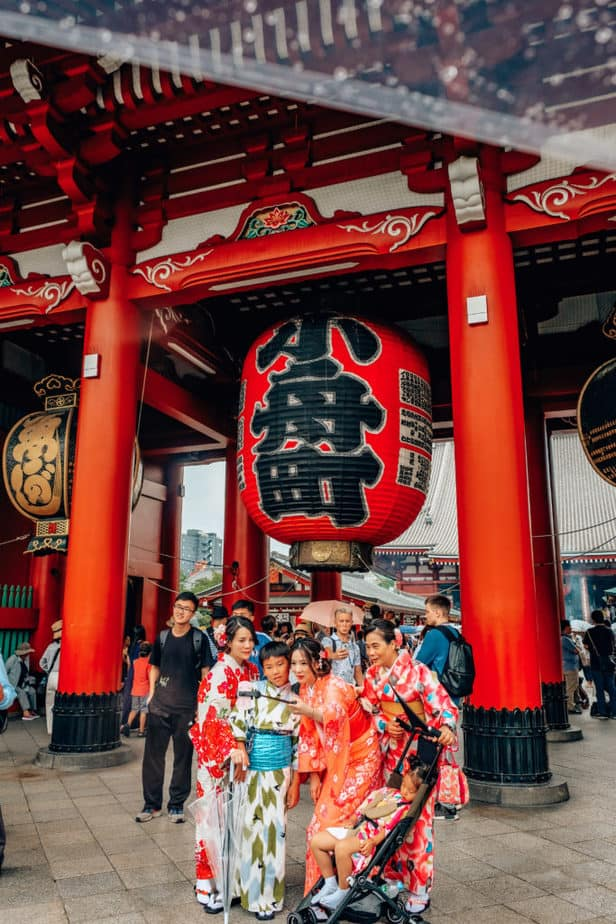 A group of people dressed as Geishas stand in front of Senso-Ji Temple