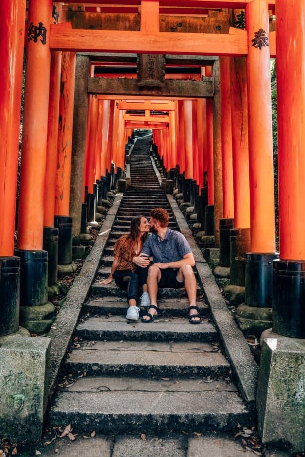 A couple sitting in the Fushimi Inari Taisha Shrine in Kyoto, Japan